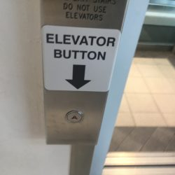 Bad planning and design in action: check out these duelling buttons and signs at Oakridge Mall